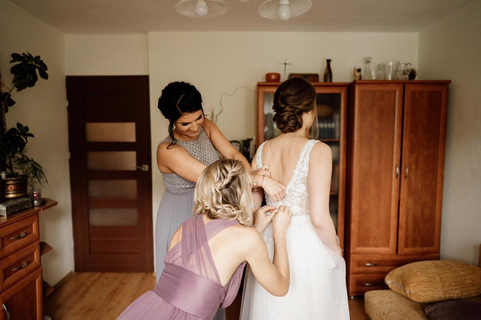 panna młoda z druhnami- zapinanie sukni ślubnej