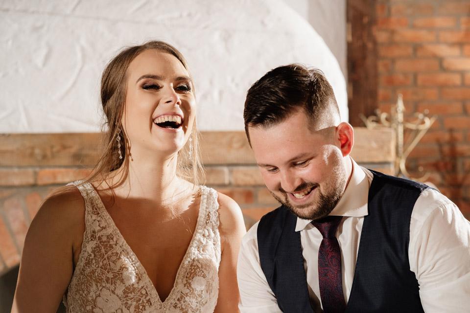 uśmiechnięta para młoda podczas krojenia tortu weselnego