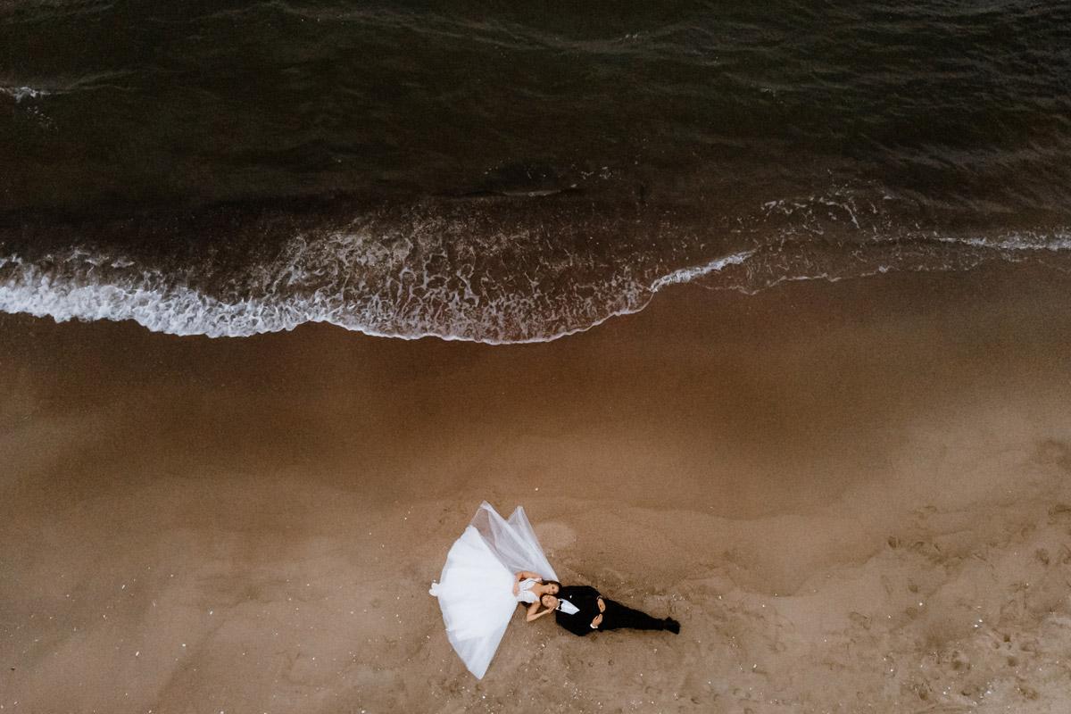 zdjęcie pary młodej z drona nad morzem